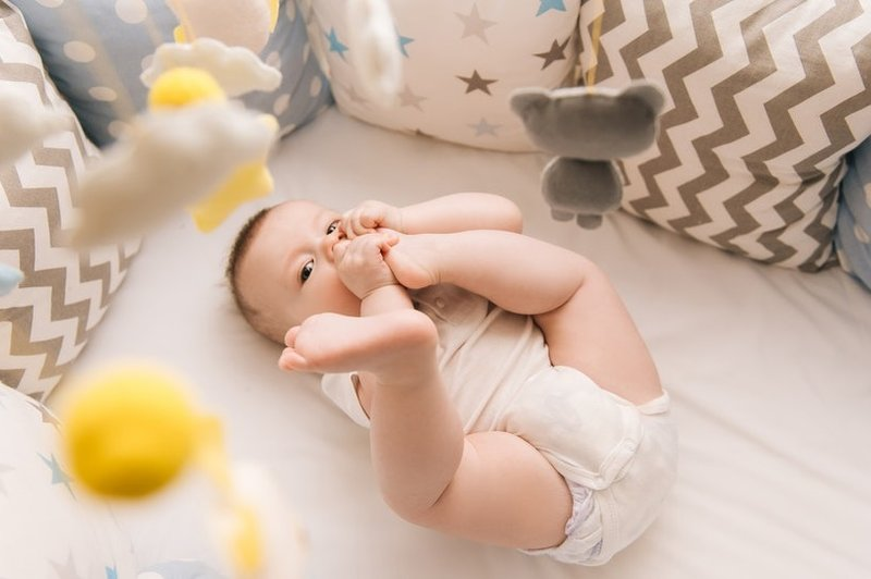 bayi memasukkan kaki ke mulut