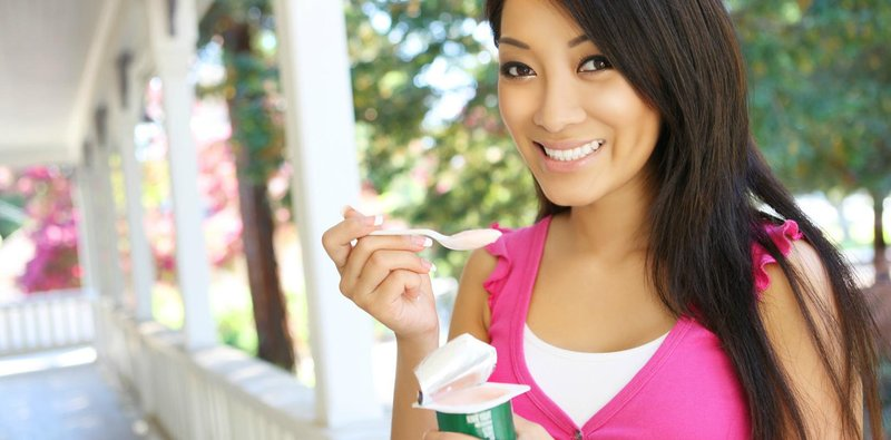a pretty asian woman at home eating yogurt 1620x800
