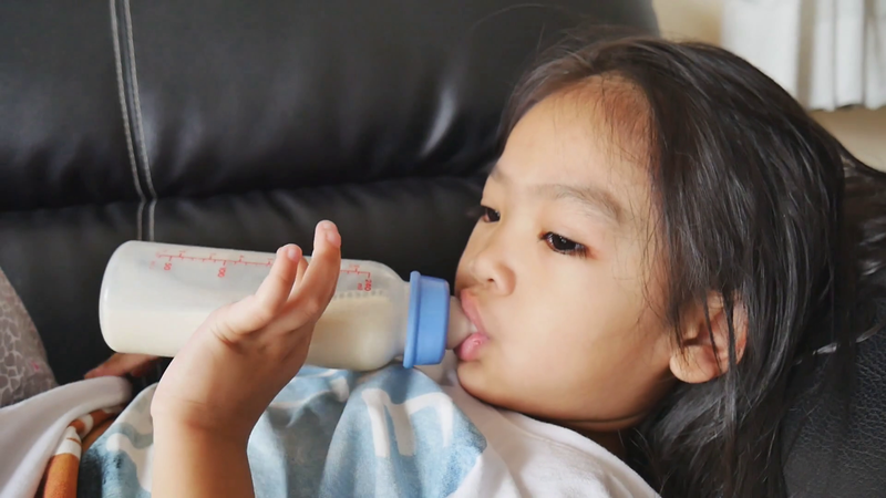 baby 4 years old happy to drink milk from milk bottle asian children drink milk from milk bottle in living room bqx1c1lrfx thumbnail full01