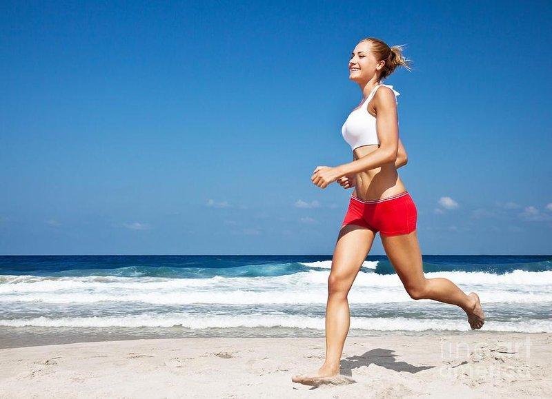 healthy woman running on the beach anna omelchenko
