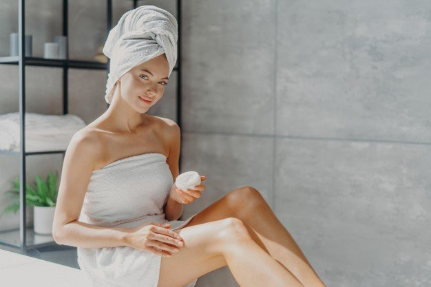 horizontal-shot-pretty-woman-applies-cosmetic-cream-skin-poses-wrapped-towel-undergoes-beauty-procedures-after-taking-shower-poses-home-bathroom_95891-3332.jpg
