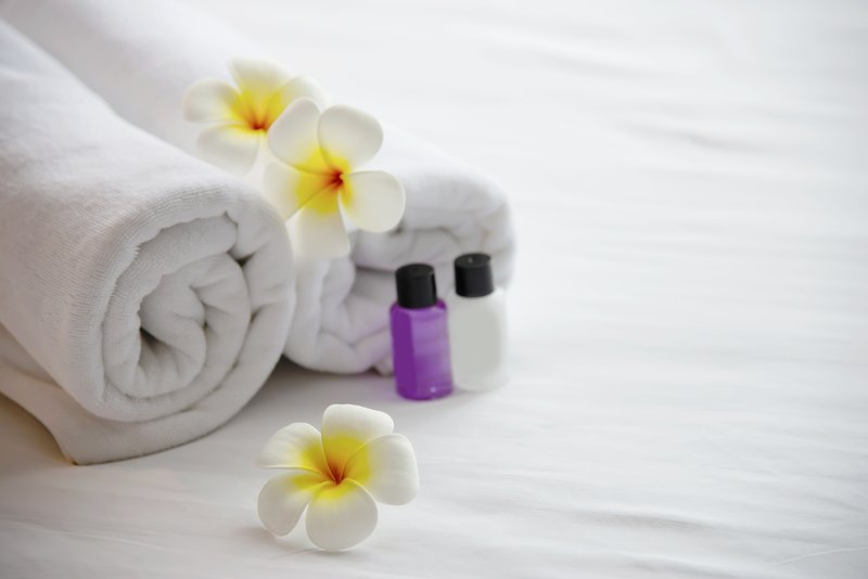 hotel-towel-shampoo-soap-bath-bottle-set-white-bed-with-plumeria-flower-decorated-relax-vacation-hotel-resort-concept.jpg
