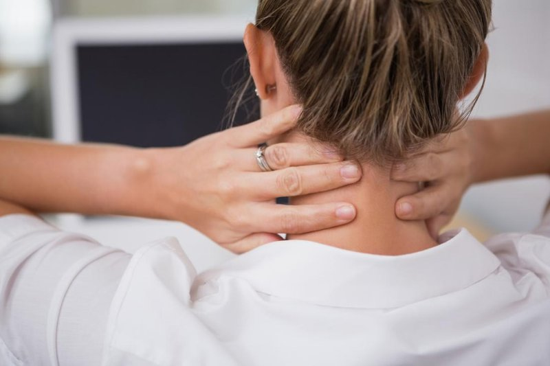 lady holding her neck in discomfort