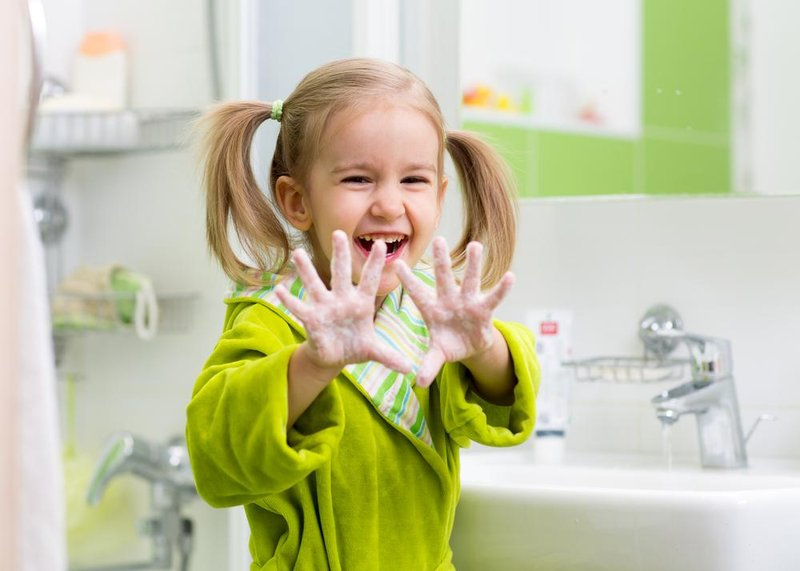little girl having fun while washing her hands