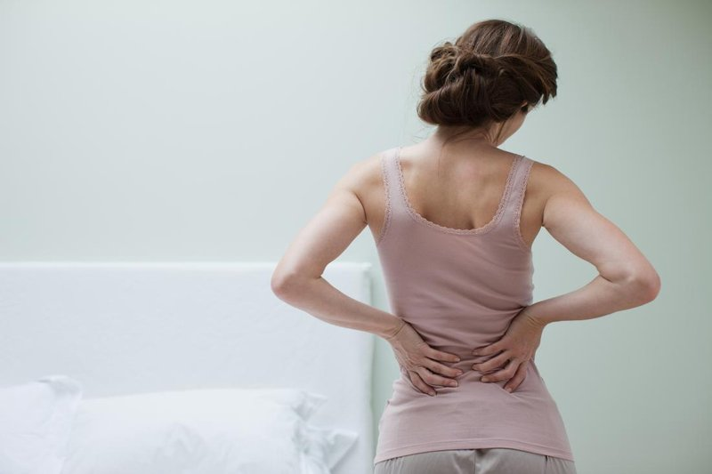 middle back pain in woman holding her back