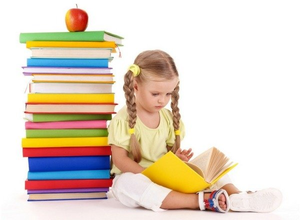 preschooler-girl-reading-a-book-sitting-next-to-a-pile-of-books-with-an-apple.jpg