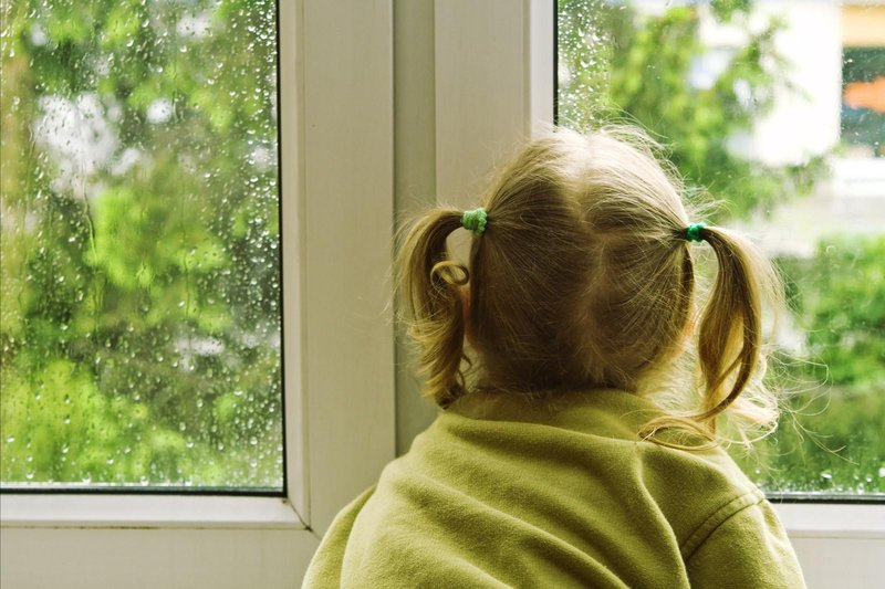 rainy day kid looks out window