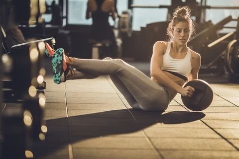 sportswoman-doing-sit-ups-with-medicine-ball-on-royalty-free-image-1040221548-1548258778.jpg