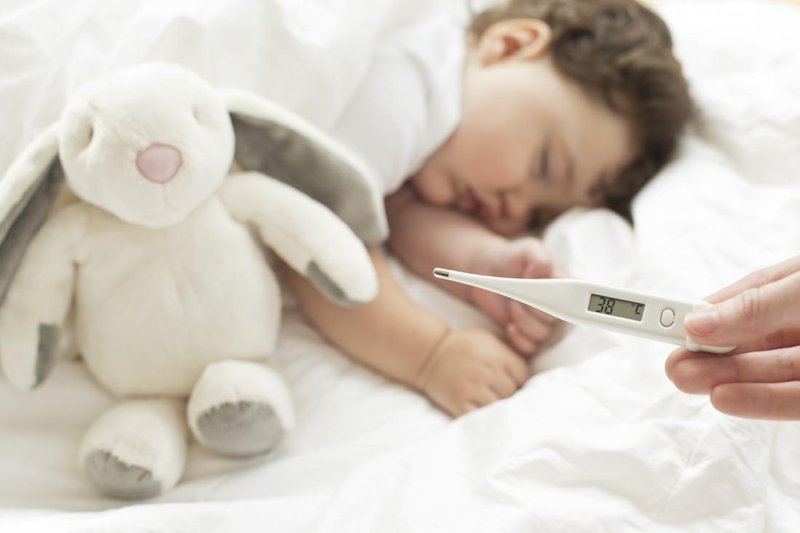 toddler asleep with a temperature monitor in foreground showing fever