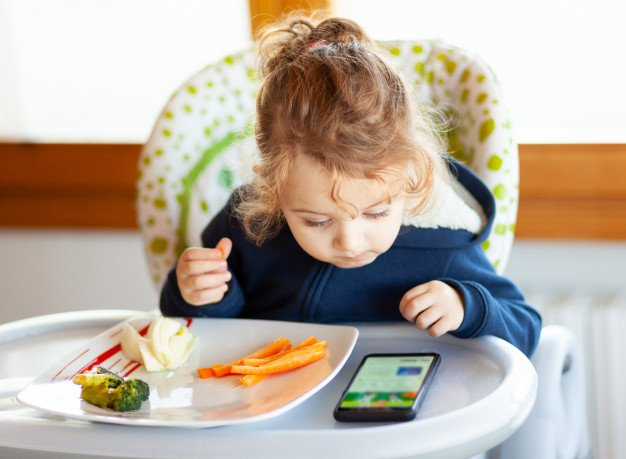 toddler-eats-while-watching-movies-mobile-phone_87414-1835.jpg