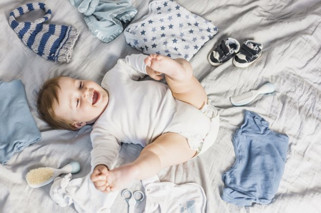 top-view-blonde-baby-surrounded-by-clothes_23-2147983486.jpg