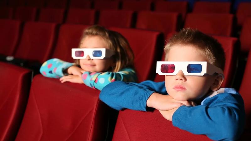 two children boy and girl watching a 3d movie in cinema m1hpu 2u f0000