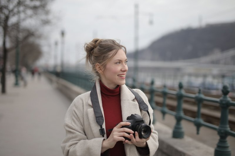 woman-wearing-a-coat-holding-black-dslr-camera-3884535.jpg