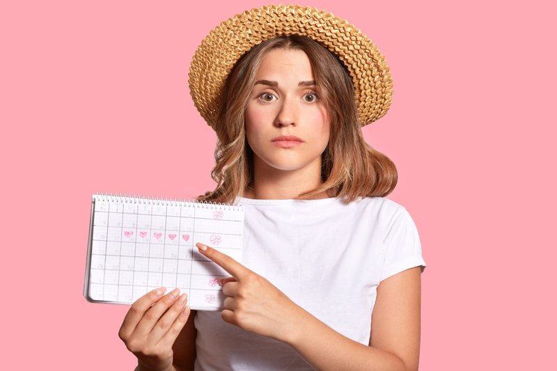 woman-with-appealing-look-holds-periods-calendar-checking-menstruation-days-points-with-fore-finger.jpg