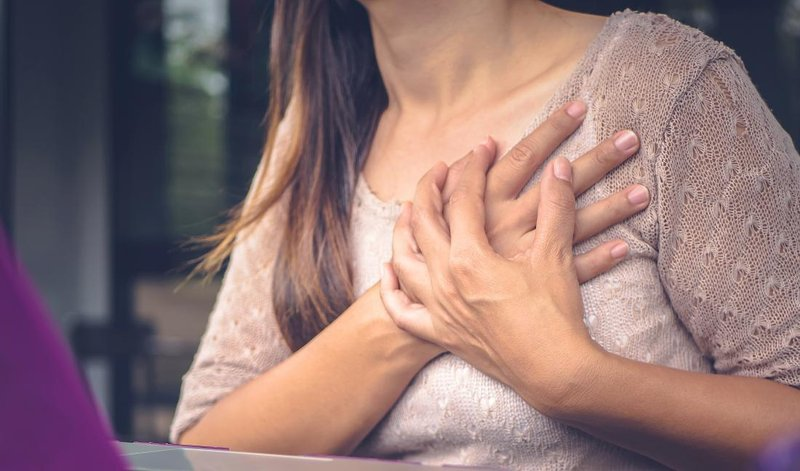 woman with chest pains clutching her chest while sitting at desk