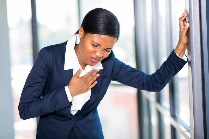 young business woman holding chest appearing to have heart attack 1024x683