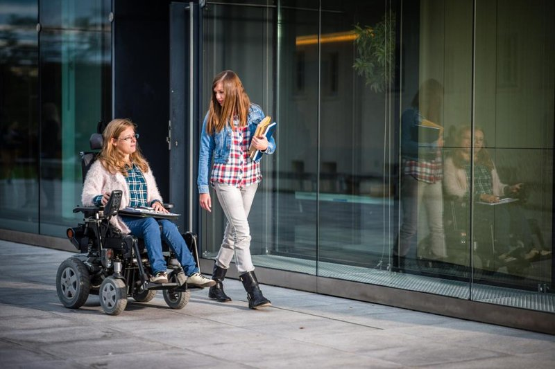 young woman with multiple sclerosis in wheelchair alongside young woman on campus